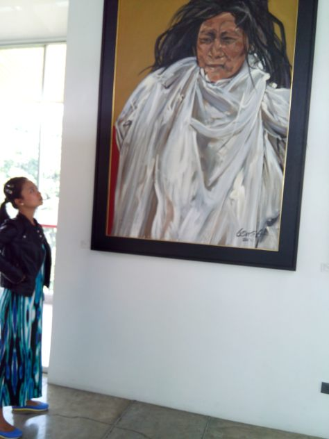 Ms. Paula Tolentino staring at one of National Artist Ben Cab's paintings.